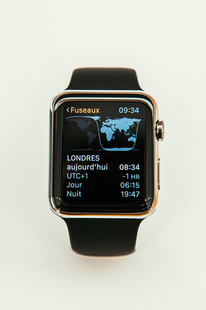 incorporates: PARIS, FRANCE – APR 10, 2015: New wearable computer Apple Watch smartwatch displaying the new Time Zone App. Apple Watch incorporates fitness tracking and health-oriented capabilities and  integration with iOS Apple products and services