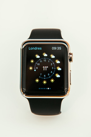 PARIS, FRANCE – APR 10, 2015: New wearable computer Apple Watch smartwatch displaying the new Weather App. Apple Watch incorporates fitness tracking and health-oriented capabilities and  integration with iOS Apple products and services Editorial