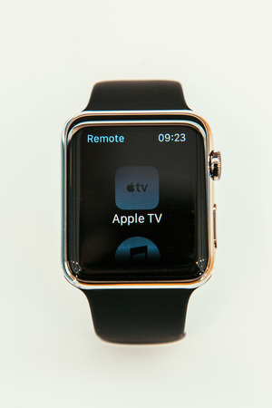 serv: PARIS, FRANCE – APR 10, 2015: New wearable computer Apple Watch smartwatch displaying the new Remmote App with Apple TV Control. Apple Watch incorporates fitness tracking and health-oriented capabilities and  integration with iOS Apple products and serv