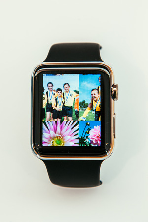 incorporates: PARIS, FRANCE – APR 10, 2015: New wearable computer Apple Watch smartwatch displaying the new Photo App. Apple Watch incorporates fitness tracking and health-oriented capabilities and  integration with iOS Apple products and services Editorial