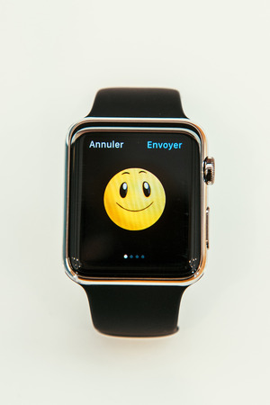 capabilities: PARIS, FRANCE – APR 10, 2015: New wearable computer Apple Watch smartwatch displaying the new Smile Emoji. Apple Watch incorporates fitness tracking and health-oriented capabilities and  integration with iOS Apple products and services