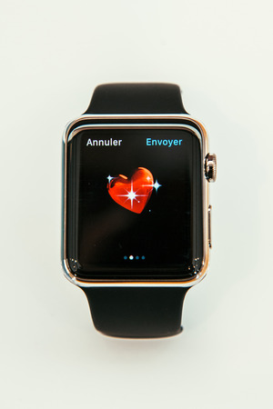 new love: PARIS, FRANCE – APR 10, 2015: New wearable computer Apple Watch smartwatch displaying the new  Love Emoji. Apple Watch incorporates fitness tracking and health-oriented capabilities and  integration with iOS Apple products and services Editorial