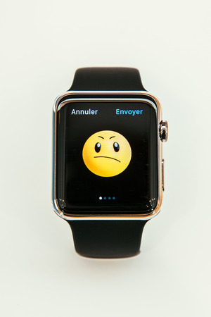 incorporates: PARIS, FRANCE – APR 10, 2015: New wearable computer Apple Watch smartwatch displaying the new Bad Face emoji. Apple Watch incorporates fitness tracking and health-oriented capabilities and  integration with iOS Apple products and services