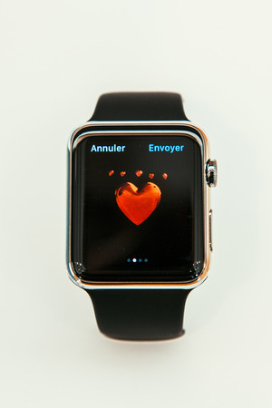 incorporates: PARIS, FRANCE – APR 10, 2015: New wearable computer Apple Watch smartwatch displaying the new  Love Emoji. Apple Watch incorporates fitness tracking and health-oriented capabilities and  integration with iOS Apple products and services Editorial