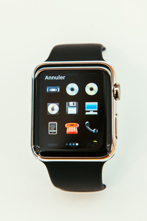 incorporates: PARIS, FRANCE – APR 10, 2015: New wearable computer Apple Watch smartwatch displaying the new Communication Emoji. Apple Watch incorporates fitness tracking and health-oriented capabilities and  integration with iOS Apple products and services