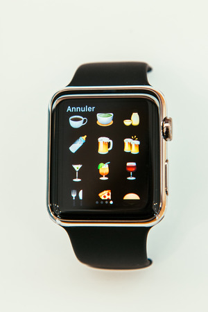 incorporates: PARIS, FRANCE – APR 10, 2015: New wearable computer Apple Watch smartwatch displaying the new  food and drinks emoji. Apple Watch incorporates fitness tracking and health-oriented capabilities and  integration with iOS Apple products and services Editorial