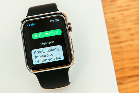 PARIS, FRANCE – APR 10, 2015: New wearable computer Apple Watch smartwatch displaying the new Message App. Apple Watch incorporates fitness tracking and health-oriented capabilities and  integration with iOS Apple products and services