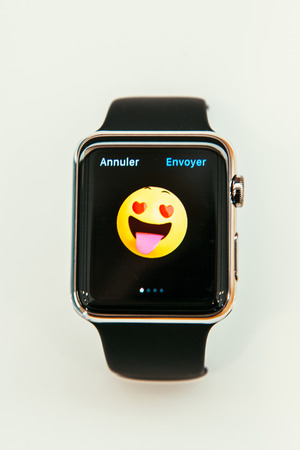 incorporates: PARIS, FRANCE – APR 10, 2015: New wearable computer Apple Watch smartwatch displaying the new Happy Love emoji. Apple Watch incorporates fitness tracking and health-oriented capabilities and  integration with iOS Apple products and services