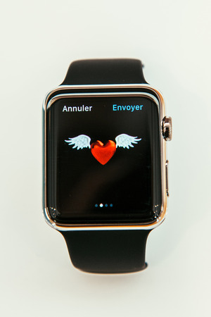 PARIS, FRANCE – APR 10, 2015: New wearable computer Apple Watch smartwatch displaying the new  . Apple Watch incorporates fitness tracking and health-oriented capabilities and  integration with iOS Apple products and services