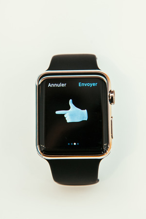 PARIS, FRANCE – APR 10, 2015: New wearable computer Apple Watch smartwatch displaying the new Left Hand emoji. Apple Watch incorporates fitness tracking and health-oriented capabilities and  integration with iOS Apple products and services Editorial