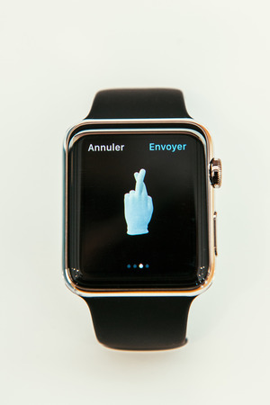 incorporates: PARIS, FRANCE – APR 10, 2015: New wearable computer Apple Watch smartwatch displaying the new Lucky Emoji. Apple Watch incorporates fitness tracking and health-oriented capabilities and  integration with iOS Apple products and services