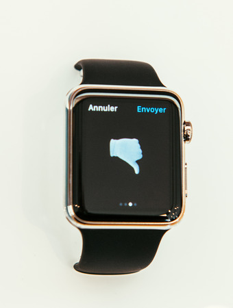 incorporates: PARIS, FRANCE – APR 10, 2015: New wearable computer Apple Watch smartwatch displaying the new Not Ok sign. Apple Watch incorporates fitness tracking and health-oriented capabilities and  integration with iOS Apple products and services