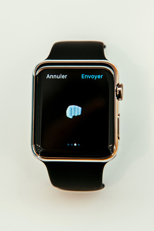 PARIS, FRANCE – APR 10, 2015: New wearable computer Apple Watch smartwatch displaying the new Fist Emoji  . Apple Watch incorporates fitness tracking and health-oriented capabilities and  integration with iOS Apple products and services