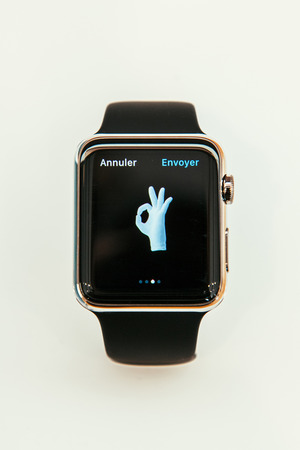 capabilities: PARIS, FRANCE – APR 10, 2015: New wearable computer Apple Watch smartwatch displaying the new OK Sign emoji. Apple Watch incorporates fitness tracking and health-oriented capabilities and  integration with iOS Apple products and services