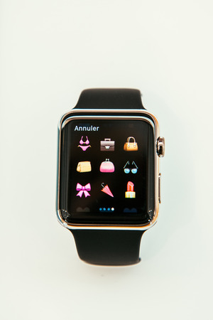 PARIS, FRANCE – APR 10, 2015: New wearable computer Apple Watch smartwatch displaying the new clothes and shopping emoji. Apple Watch incorporates fitness tracking and health-oriented capabilities and  integration with iOS Apple products and services