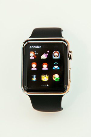 incorporates: PARIS, FRANCE – APR 10, 2015: New wearable computer Apple Watch smartwatch displaying the new Beauty Emoji. Apple Watch incorporates fitness tracking and health-oriented capabilities and  integration with iOS Apple products and services