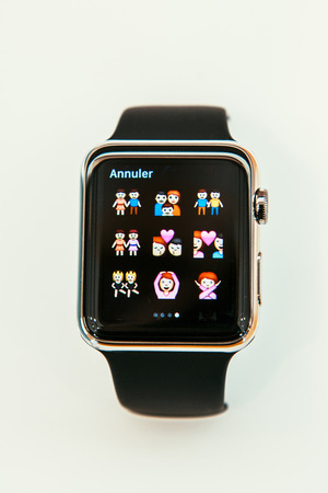 incorporates: PARIS, FRANCE – APR 10, 2015: New wearable computer Apple Watch smartwatch displaying the new Family Emoji  . Apple Watch incorporates fitness tracking and health-oriented capabilities and  integration with iOS Apple products and services