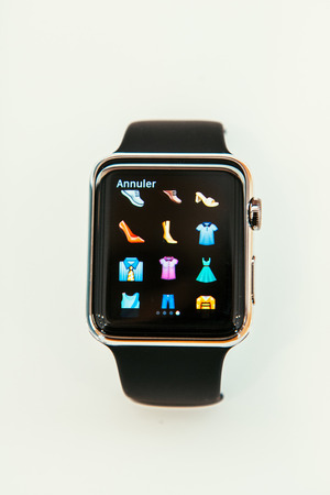 incorporates: PARIS, FRANCE – APR 10, 2015: New wearable computer Apple Watch smartwatch displaying the new clothes emoji. Apple Watch incorporates fitness tracking and health-oriented capabilities and  integration with iOS Apple products and services Editorial