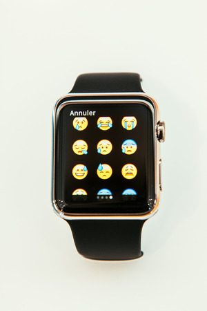 incorporates: PARIS, FRANCE – APR 10, 2015: New wearable computer Apple Watch smartwatch displaying the new crying emoji. Apple Watch incorporates fitness tracking and health-oriented capabilities and  integration with iOS Apple products and services