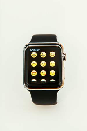 incorporates: PARIS, FRANCE – APR 10, 2015: New wearable computer Apple Watch smartwatch displaying the new emoji faces. Apple Watch incorporates fitness tracking and health-oriented capabilities and  integration with iOS Apple products and services