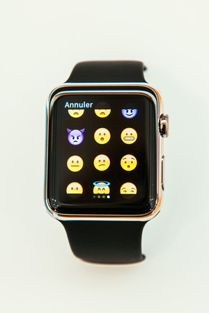 PARIS, FRANCE – APR 10, 2015: New wearable computer Apple Watch smartwatch displaying the new set of emoji. Apple Watch incorporates fitness tracking and health-oriented capabilities and  integration with iOS Apple products and services