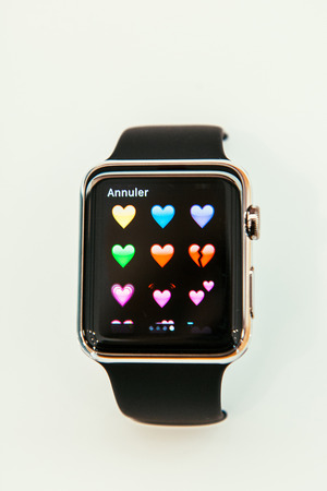 incorporates: PARIS, FRANCE – APR 10, 2015: New wearable computer Apple Watch smartwatch displaying the new Hearts Emoji. Apple Watch incorporates fitness tracking and health-oriented capabilities and  integration with iOS Apple products and services