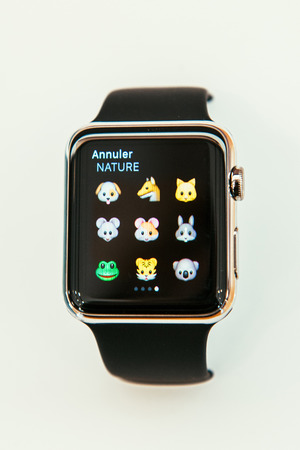 incorporates: PARIS, FRANCE – APR 10, 2015: New wearable computer Apple Watch smartwatch displaying the new Animals Emoji. Apple Watch incorporates fitness tracking and health-oriented capabilities and  integration with iOS Apple products and services