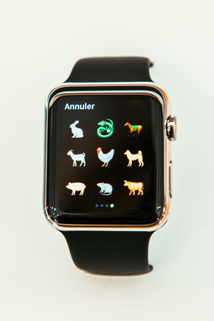 capabilities: PARIS, FRANCE – APR 10, 2015: New wearable computer Apple Watch smartwatch displaying the new Farm Animals Emoji. Apple Watch incorporates fitness tracking and health-oriented capabilities and  integration with iOS Apple products and services