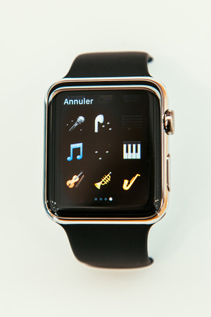 capabilities: PARIS, FRANCE – APR 10, 2015: New wearable computer Apple Watch smartwatch displaying the new musical instruments emoji. Apple Watch incorporates fitness tracking and health-oriented capabilities and  integration with iOS Apple products and services