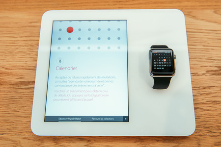 PARIS, FRANCE – APR 10, 2015: New wearable computer Apple Watch smartwatch displaying the new Calendar App. Apple Watch incorporates fitness tracking and health-oriented capabilities and  integration with iOS Apple products and services Editorial