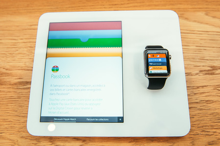 incorporates: PARIS, FRANCE – APR 10, 2015: New wearable computer Apple Watch smartwatch displaying the new Passbook App. Apple Watch incorporates fitness tracking and health-oriented capabilities and  integration with iOS Apple products and services