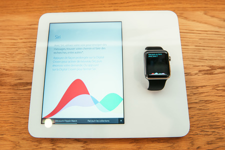 incorporates: PARIS, FRANCE – APR 10, 2015: New wearable computer Apple Watch smartwatch displaying the new Siri App . Apple Watch incorporates fitness tracking and health-oriented capabilities and  integration with iOS Apple products and services