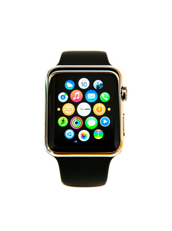 PARIS, FRANCE - APRIL 10, 2015: Apple Watch smartwatch the 38mm 18-Carat Yellow Gold Case with Bright Black Modern Buckle. Apple Watch has multiple fitness tracking and health-oriented capabilities and integration with iOS Apple products and services