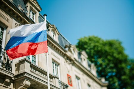 consulate: STRASBOURG, FRANCE - APRIL 18, 2015: Russian Federation flag waving in front of Consulate of Russia in Strasbourg, France. Tilt shift lens used to accent the flag for more natural effect