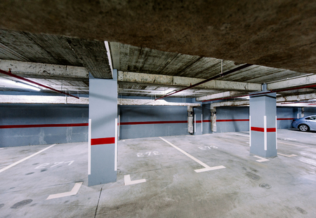 Empty underground car park with a solitaire car in the right corner photo