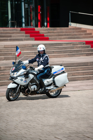 motorcycle officer: STRASBOURG, FRANCE - APRIL 21, 2015: Official delegation police man inext to the red carpet in front of European Court of Human Rights Editorial