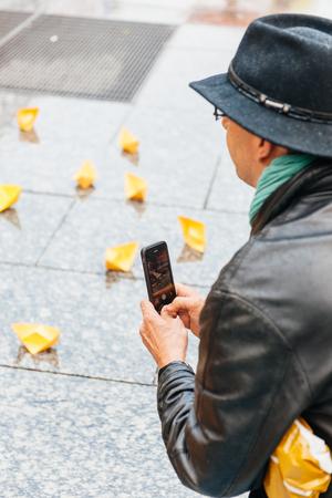 conflictos sociales: ESTRASBURGO, FRANCIA - 26 de abril 2015: El hombre fotografiando barcos de papel amarillo en protesta contra la pol�tica de inmigraci�n y gesti�n de fronteras que pide compromiso a ra�z de los desastres en barco migrantes Editorial