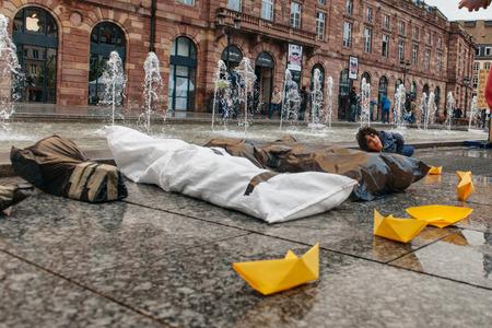 conflictos sociales: ESTRASBURGO, FRANCIA - 26 de abril 2015: T�teres de cuerpos muertos y barcos de papel amarillo en protesta contra la pol�tica de inmigraci�n y gesti�n de fronteras que pide compromiso a ra�z de los desastres en barco migrantes