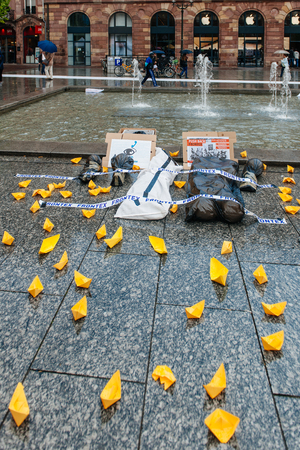 corpses: STRASBOURG, FRANCE - APR 26 2015: Yellow paper boats sand dead corpses at protest against immigration policy and border management which asks for commitment in the wake of migrants boat disasters