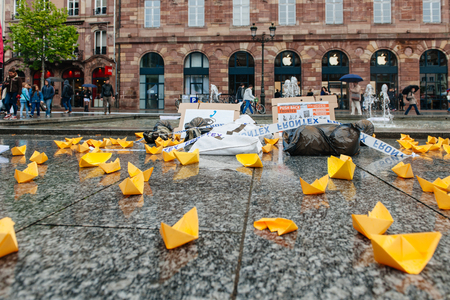 corpses: STRASBOURG, FRANCE - APR 26 2015: Yellow paper boats and dead corpses at protest against immigration policy and border management which asks for commitment in the wake of migrants boat disasters Editorial