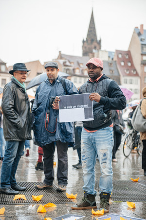 french ethnicity: STRASBOURG, FRANCE - APR 26 2015: I am a migrant poster holed by a man at protest against immigration policy and border management which asks for commitment in the wake of migrants boat disasters