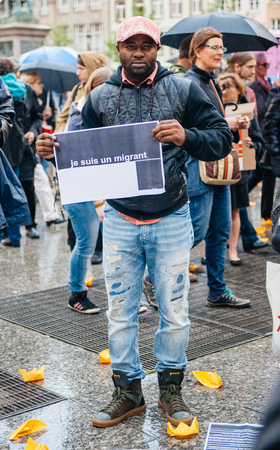 holed: STRASBOURG, FRANCE - APR 26 2015: I am a migrant poster holed by a man at protest against immigration policy and border management which asks for commitment in the wake of migrants boat disasters
