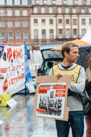 social conflicts: ESTRASBURGO, FRANCIA - 26 de abril 2015: Hombre que sostiene el cartel en protesta contra la pol�tica de inmigraci�n y gesti�n de fronteras que pide compromiso a ra�z de los desastres en barco migrantes