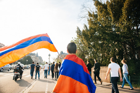 genocide: STRASBOURG, FRANCE - APRIL 24, 2015: Armenian flag waving by a kid while the protesters march for 100th remembrance year of Armenian genocide in 1915 as part of Armenian Genocide Remembrance Day