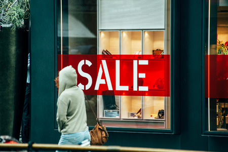buying shoes: VIENA, Austria - 05 de julio 2011: La mujer pasa delante del gran ventanal de la tienda de lujo con rojo en letras blancas VENTA. Viena es una atracci�n magn�tica para los turistas de todas partes del mundo para ir de compras