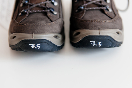 rubber lining: Front view of mountain boots with 7,5 size marked on both of them Stock Photo