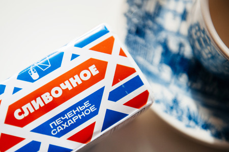 archival: MOSCOW, RUSSIA - SEP 11, 2014: Traditional russian biscuit Slivochnoye Pechenye next to a tea cup.
