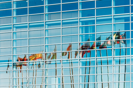 European Union countries flags reflected in European Parliament facade in Strasbourg France Alsace