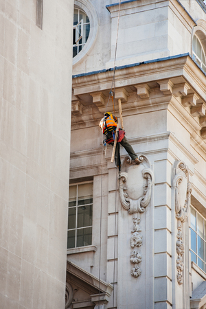 high up: Construction worker lowers himself into position to perform maintenance high up of a building in London while using safety equipment and providing job security