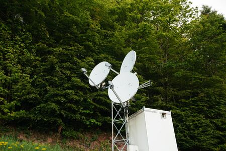 communication breakdown: Three satellite dish on a communication tower in the middle of a green forest Stock Photo